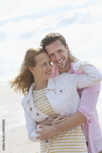 Portrait of smiling young couple hugging on sunny beach