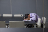Businessman sleeping on laptop in conference room
