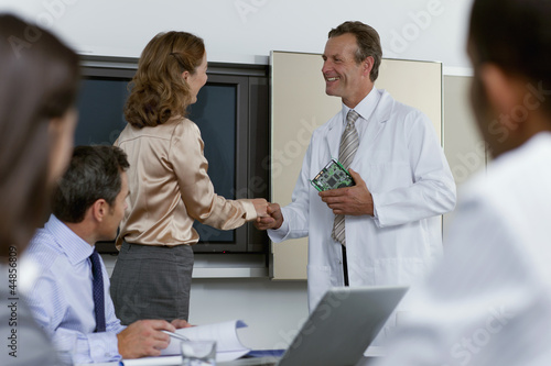 Engineer and businesswoman shaking hands in conference room