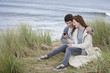 Teenage couple reading text message in grass on beach