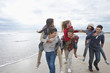 Enthusiastic teenage friends piggybacking on beach