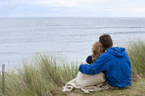 Teenage couple hugging in grass and looking at ocean view