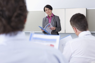 Businesswoman holding report and leading meeting in conference room
