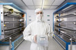 Portrait of scientist in clean suit holding container in silicon wafer manufacturing laboratory