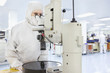 Scientist in clean suit using microscope in silicon wafer manufacturing laboratory