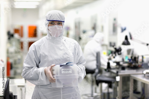 Portrait of scientist in clean suit carrying container in silicon wafer manufacturing laboratory