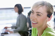Close up of smiling businesswoman wearing headset in office with co-worker in background