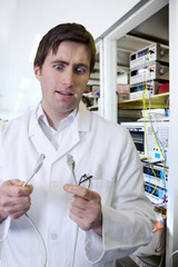 Wide-eyed engineer holding computer data cable in laboratory