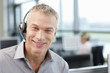Portrait of smiling businessman wearing headset in office