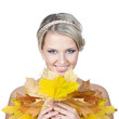 Young blonde woman with autumn leaves in hand