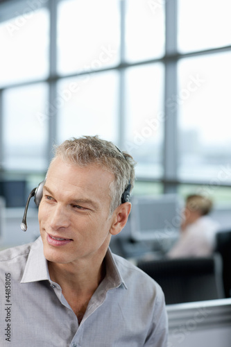 Smiling businessman wearing headset in office