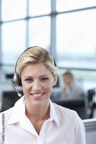 Portrait of smiling businesswoman wearing headset in office