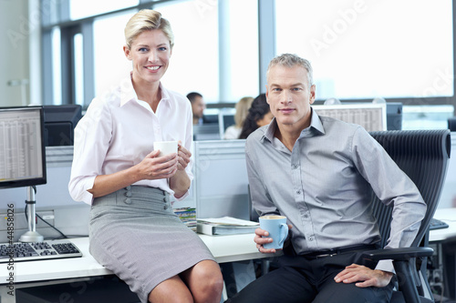 Portrait of smiling businessman and businesswoman drinking coffee in office