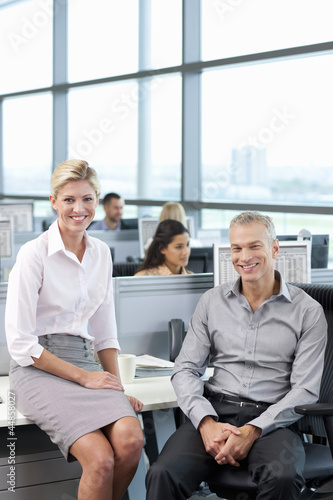 Portrait of smiling businessman and businesswoman in office with co-workers