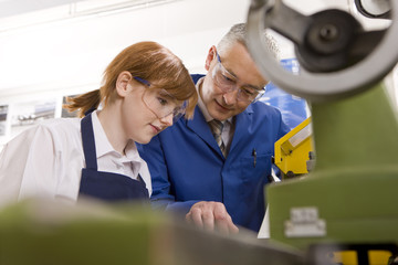 Teacher explaining to student how to use lathe in metalwork class