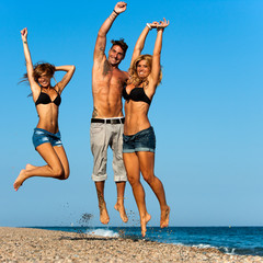 Energetic friends jumping on beach.