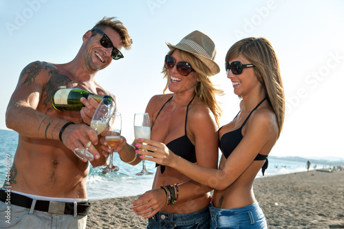 Group of young friends celebrating on beach.