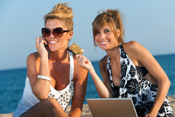Two girlfriends shopping on line at beach.