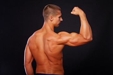An athletic man is demonstrating his biceps