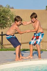 Kinder spielen am Swimmingpool - Jungen stoßen sich in den Pool