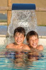 Zwei Jungen unter dem Wasserstrahl im Swimmingpool - Abkühlung