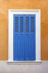Mediterranean window with closed shutters.