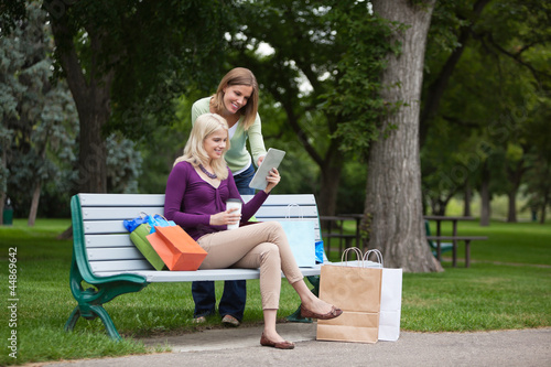 Women With Shopping Bags Using Tablet PC At Park