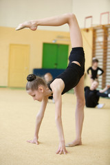 young gymnast stretching and training