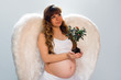 Pregnant angelic woman on white background with small tree