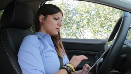 Young businesswoman with tablet in traffic jam