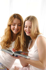two young women reading book back to back on bed