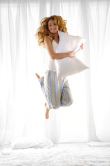 Happy blond woman holding pillow jumping on her bed