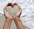 canvas print picture - Mellow heart shaping female hands at beach