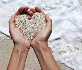 Mellow heart shaping female hands at beach