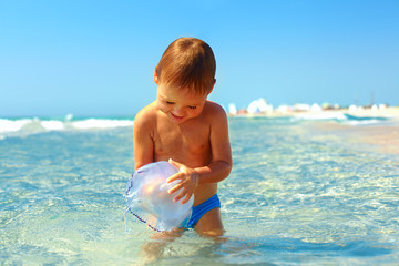 curious baby boy catches jellyfish in the sea