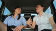 Pretty businesswomen laughing on the back seats of car