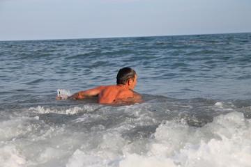мужчина плавает в море