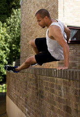 Athletic man jumping over a wall