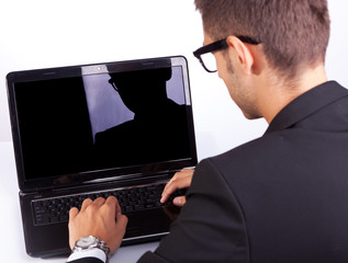 back view of a business man working at laptop