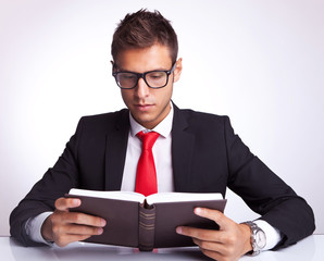 business man wearing glasses reading a book
