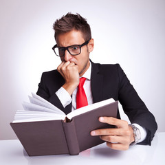 business man being affraid by the action of the book