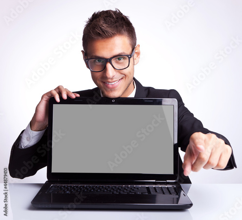 man sitting at office desk with laptop pointing