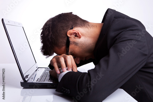 Tired business man sleeping on laptop