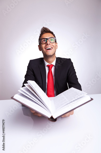 man opening a book with lots of knowledge wonders