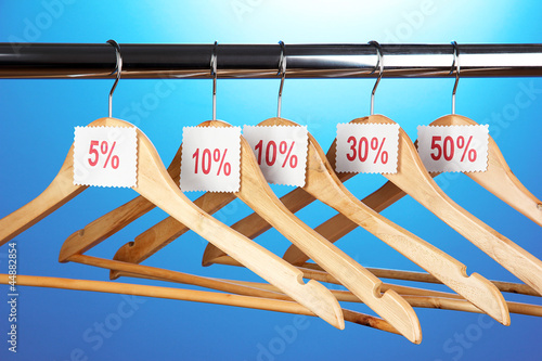 wooden clothes hangers as sale symbol on blue background.