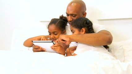 Young Ethnic Single Father Children Using Wireless Tablet Bed
