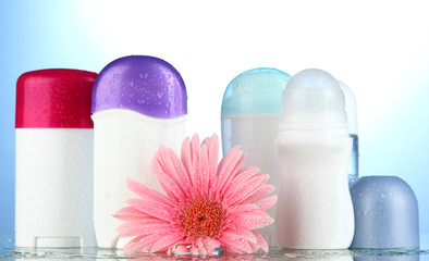 deodorant botttles with flower on blue background