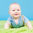 Baby mit blauem Hintergrund und grüner Decke