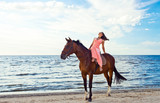 girl in dress with horse on seacoast