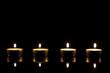 vier teelichter vor schwarzem hintergrund